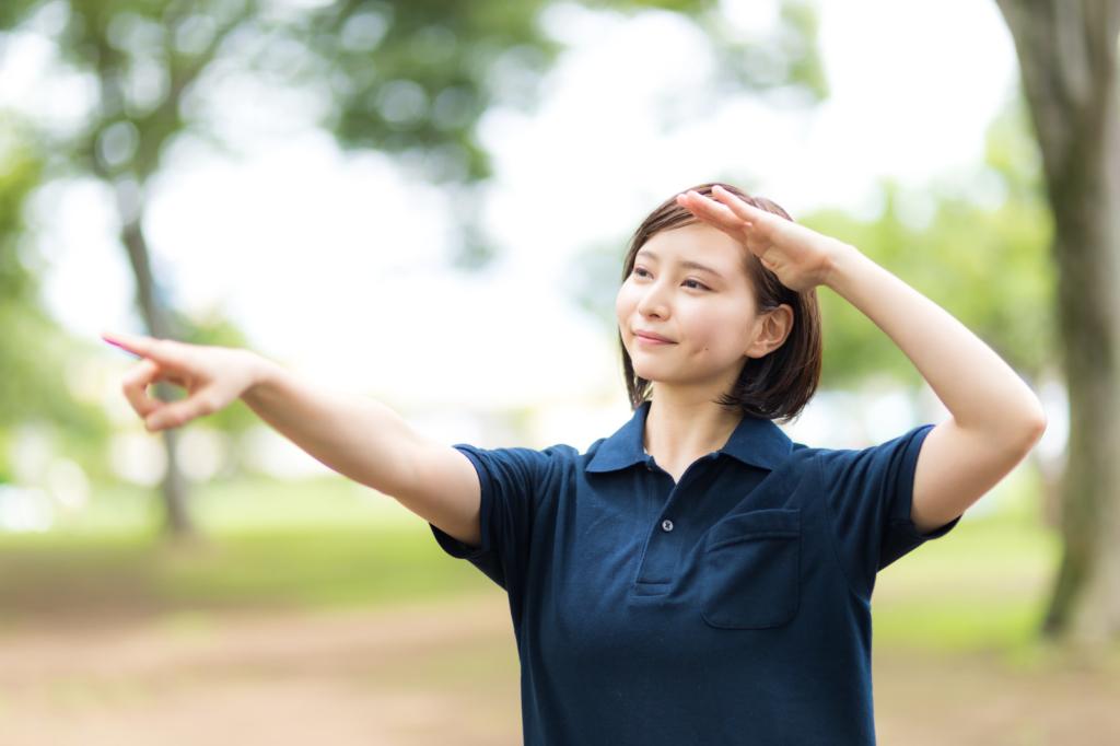 熱中症を気にして日陰を指差すヘルパーの女性 [モデル:yumiko]